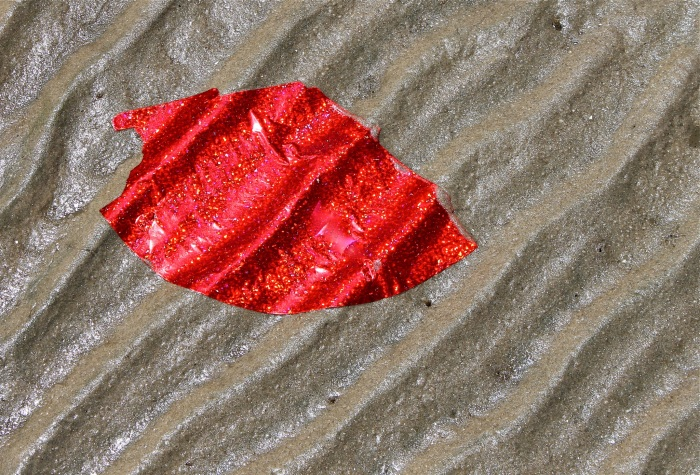 Red glitter foil moulds itself to rippled sands